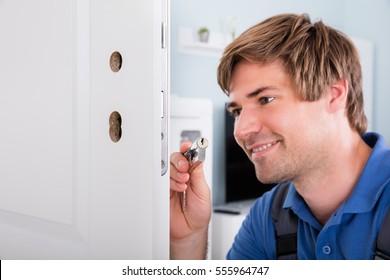 Happy Young Carpenter Fixing Broken Door Lock
