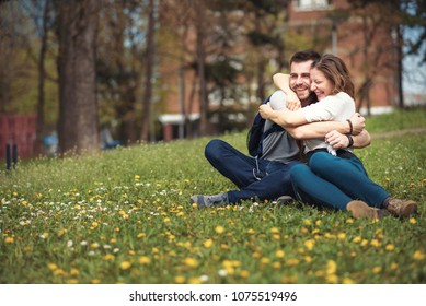 Happy young casual couple enjoying their time together in a grassy field covered with dandelions, celebrating spring time