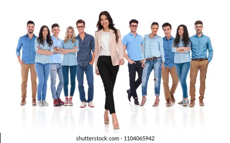 happy young casual group with businesswoman leader walking in front of them on white background