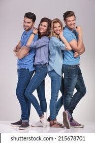 happy young casual group of people standing together and smile on grey studio background