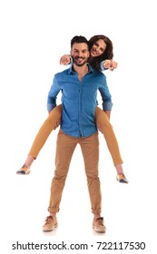 happy young casual man carrying his woman while she is pointing to the camera on white background