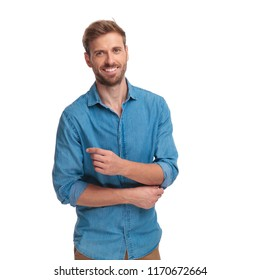 happy young casual man fixing his sleeve on white background