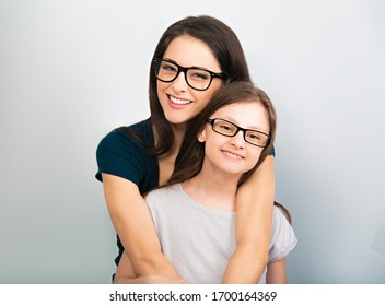 Happy young casual mother and smiling kid in fashion glasses hugging on light blue background with empty copy space. Closeup studio portrait