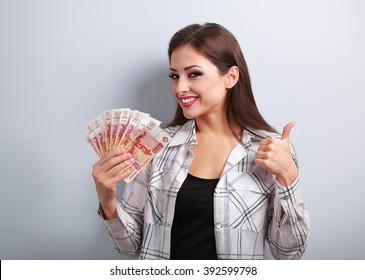 Happy young casual woman in glasses holding roubles and showing thumb up sign with toothy smiling on blue background