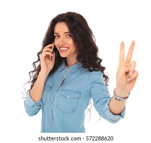 happy young casual woman making victory sign while talking on the phone on white background