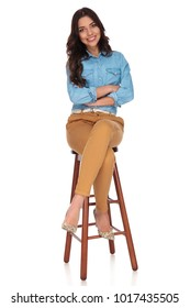 happy young casual woman sitting on a stool with hands crossed on white background