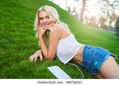 Happy young Caucasian blonde woman with tablet in park on sunny day on grass. Modern lifestyle and relaxation concepts.
