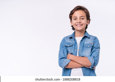 Happy young caucasian boy in casual outfit with arms crossed isolated over white background