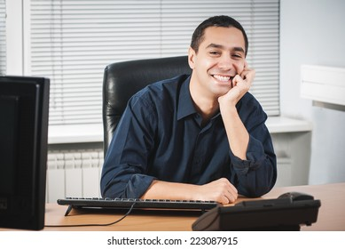 Happy young caucasian businessman in his office