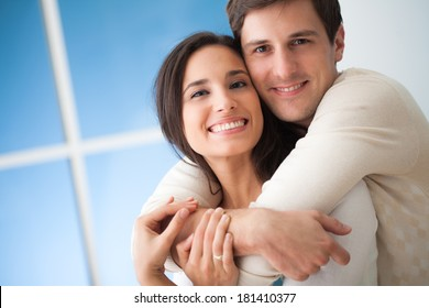Happy young Caucasian couple posing together at home.