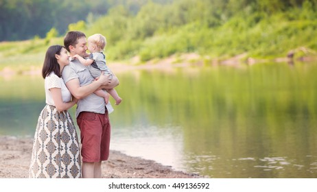 Happy young caucasian family with mom, dad and one year old boy (son) spending time together outside in green summer nature with river. Happy family concept with copy space or text on right area
