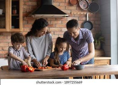 Happy young Caucasian family with two little kids have fun cooking healthy breakfast in kitchen together. Smiling parents with small children prepare diet vegetarian salad in own home in the morning.