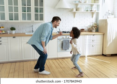 Happy young Caucasian father and little biracial daughter sing in kitchen appliances entertain at home, overjoyed dad and small African American girl child have fun play on weekend together