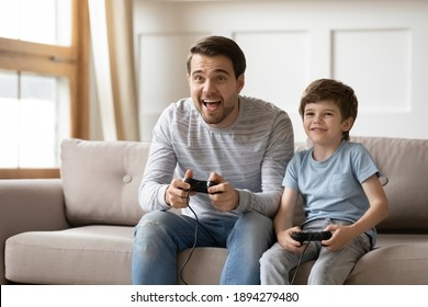 Happy young Caucasian father and little 6s son sit on couch at home have fun playing computer video game together. Overjoyed dad and small boy child enjoy family weekend engaged in funny activity.