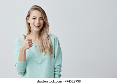 Happy young caucasian female wearing blue long sleeved shirt making thumb up sign and smiling cheerfully, showing her support and respect to someone. Body language. I like that. Good job.