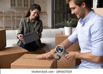 Happy young Caucasian man and woman seal wrap packages with tape dispenser relocate to new house. Smiling millennial couple renters pack boxes with adhesive scotch, moving to own home together.