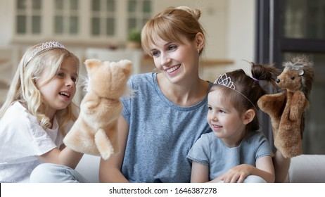 Happy young Caucasian mom play with little preschooler daughters use fluffy toys, smiling millennial mother or nanny engaged in doll theatre game with small girls children, have fun together at home