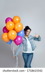 happy young caucasian woman in denim pointing at bright colorful air balloons isolated on gray background. birthday party.