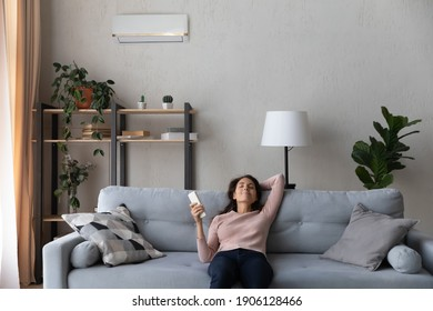 Happy young caucasian woman turning on air conditioner with controller, breathing fresh cooled air or enjoying comfortable temperature indoors, relaxing on comfortable sofa in modern living room.