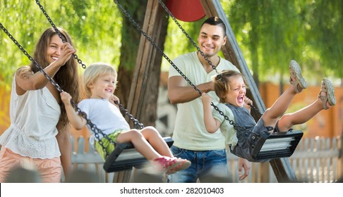 Happy young cheerful family of four at playground's swings. Focus on woman