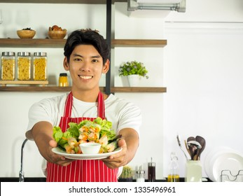 Happy young chef in red apron presenting his salad rolls dish with two hands. Inviting people to try his delicious healthy food.