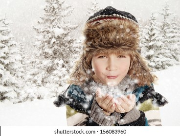 Happy young child blowing snowflakes in white winter snowy landscape