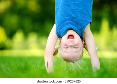 Happy young child playing head over heels on green grass in spring park