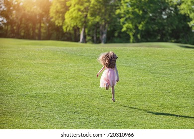 Happy young child playing on green grass in park