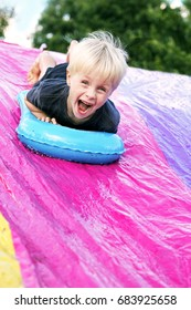 A happy young child is screaming as he slides down a slip-and-slide in his backyard.
