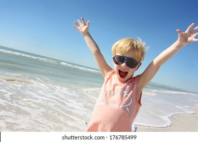 a happy young child is smiling big and raising his arms over his head in joy on vacation at the beach by the ocean shore.