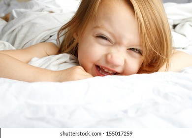 Happy young child smiling in white blankets