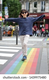 Happy young child with sunglasses walking along the colorful gay rainbow lines of the crosswalk with care and balance, cafe background, daylight