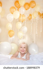 A happy young child is surrounded by white and yellow helium balloons.  Could represent party, fun, celebration