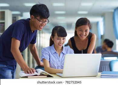 Happy young Chinese or Asian college students study together in the library with computer or laptop