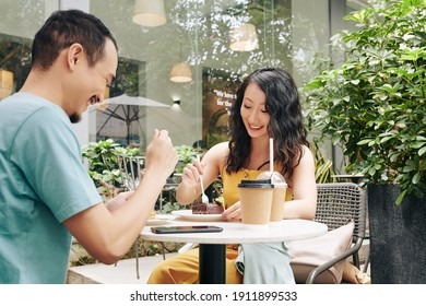 Happy young Chinese couple drinking coffee and eating desserts when having romantic date in outdoor cafe