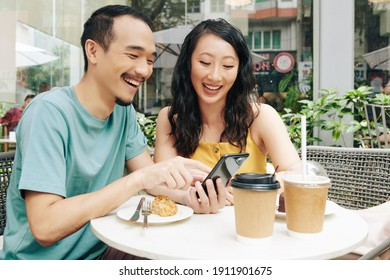Happy young Chinese couple looking at funny memes and videos on smartphone when sitting in cafe
