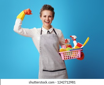 happy young cleaning woman in apron with a basket with cleansers and brushes showing biceps against blue background. cleaner shows power of her professional training in the field of cleaning service