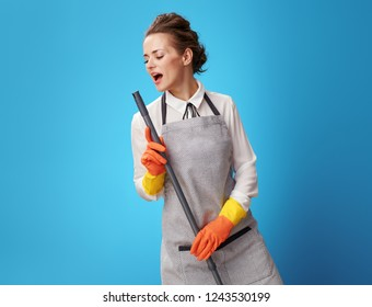 happy young cleaning woman in apron with mop singing on blue background. fun and quickly tidy up the house or office housemaid cleaning service.