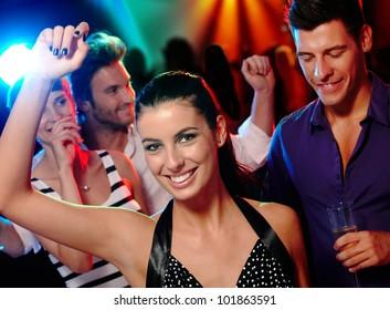 Happy young companionship having fun on dance floor.