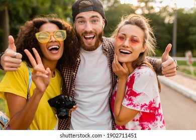 happy young company of emotional smiling friends walking in park with photo camera, man and women having fun together, colorful summer hipster fashion style, talking, smiling