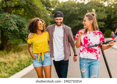 happy young company of smiling friends walking in park with electric kick scooter, man and women having fun together, colorful summer hipster fashion style, talking, smiling