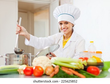 Happy young cook in white uniform  with ladle at commercial kitchen
