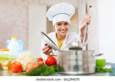 Happy young cook in white uniform works with ladle at commercial kitchen
