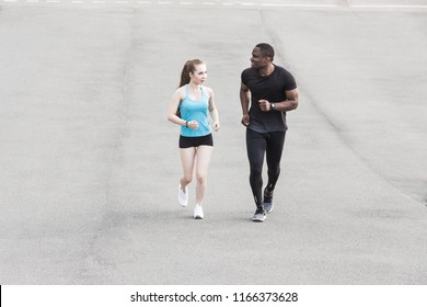 happy young couple afro-american man and european woman running together. A loving couple is run, engaged in sports, family values