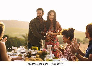 Happy young couple announcing their pregnancy at a party. Man with his girlfriend sharing surprise pregnancy announcement with friends at dinner party.