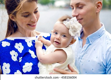 happy young couple with baby girl standing in water girl in the blue dress, boy shirt in marine style