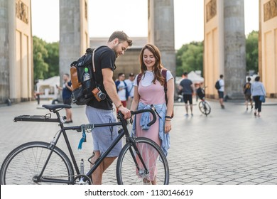 happy young couple with backpacks and bicycle at Pariser Platz, Berlin, Germany
