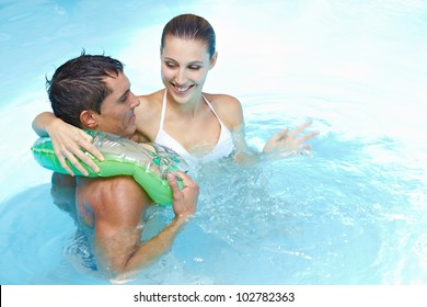 Happy young couple bathing with floating ring in swimming pool