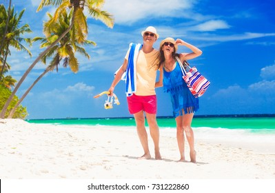 happy young couple with beach accessories having fun by the beach