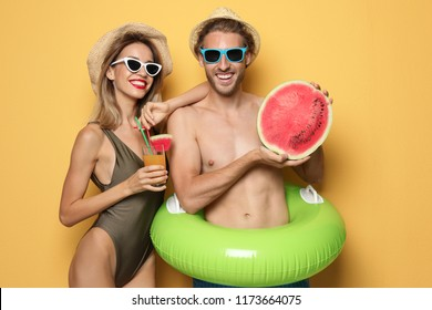 Happy young couple in beachwear with inflatable ring and cocktail on color background